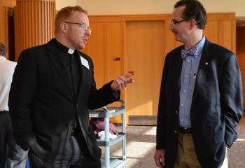 Father Mark Searles, chaplain of Allentown Central Catholic High School (ACCHS) and member of the board, chats with James MacDougall, vice chair of the board.