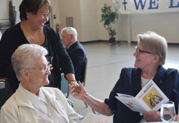 MarySue Rother greets Missionary Sisters of the Most Sacred Heart of Jesus (MSC) from Reading, Sister Mary Seibert, left, and Sister Bernard. (Photo by John Simitz)