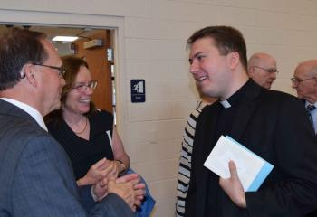 Father John Rother greets Mark Roth and Rosemary Leblond, parishioners of St. Thomas More, Allentown. (Photo by John Simitz)