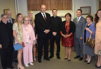 Msgr. Alfred Schlert, left, diocesan administrator, greets Father Rother and his family before the ceremony, from left: his uncle Michael Rother, his sister Gracia Rother, his grandmother Joan Rother, his aunt Marianne Bright, his father John Rother, his mother MarySue Rother, his uncle William Liaw, his grandmother Judith Liaw, and his sister Melinda Rother. (Photo by John Simitz)
