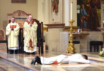 Deacon Peter Schutzler, left and Bishop Cullen chant the litany as Father Rother prostrates himself before the altar during the Litany of Supplication. (Photo by John Simitz)