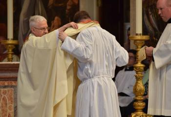 Father William Linkchorst, left, pastor emeritus of SS. Peter and Paul, Tamaqua, vests Father Rother with a stole as a sign of his authority to act in the name of Christ during Investiture with Stole and Chasuble. (Photo by John Simitz)