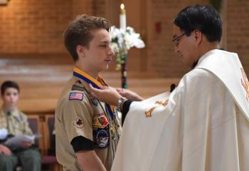 Father Eric Tolentino presents Christopher Dunlap with the Ad Altare Dei Award. (Photo by John Simitz)
