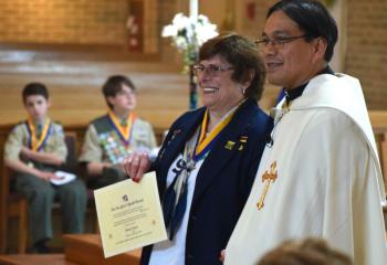 Joanne Loeper receives the For God and Youth Award from Father Eric Tolentino. (Photo by John Simitz)