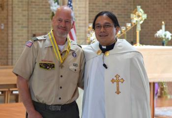 Father Eric Tolentino presents Todd McGreggor with the St. George Award. (Photo by John Simitz)