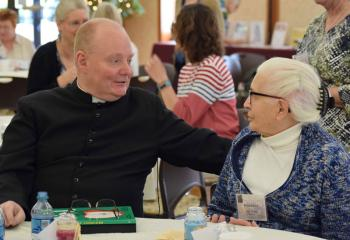 Father Brensinger talks with Rose Tucci, parishioner of Holy Rosary, Reading. (Photo by John Simitz)