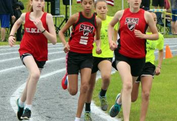 Girls run in a pack while competing in the track and field meet.