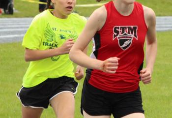 Sydney Azzalini, left, St. Jane and Isabel DeVos, St. Thomas More, race at the track and field meet. Twenty diocesan teams competed in the meet with St. Jane finishing third with a score of 108.