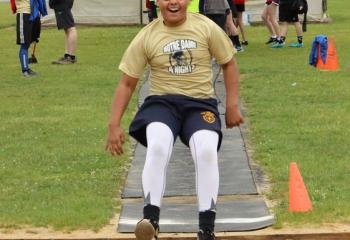Tyriek Rivera, Notre Dame of Bethlehem, descends for his landing while competing in the long jump.