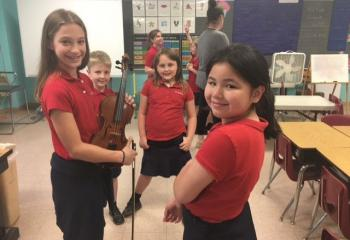 Sara Spolski, grade four, demonstrates the violin to, from left, second-graders Evan Schimpf, and Madyson Donton, and first-grader Lynn Nguyen at St. Ambrose School, Schuylkill Haven. (Photo courtesy of St. Ambrose School)