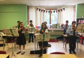 Practicing during violin lessons May 31 are, from left: front, Lily Snyder, Olivia Lesher and Colten Brown; back, Paul Zuk, Nicole Knoblauch, Dalton Seisler and Aidan Becker. (Photo courtesy of St. Ambrose School)