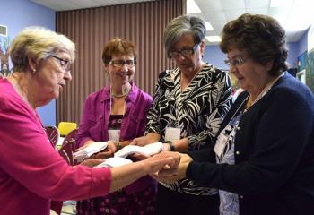 Sister of Mercy Sister Janice Marie Johnson blesses the hands of, from left, Barbara Malewski, Karen Wallace and Helen DiGirolomo. (Photo by John Simitz)