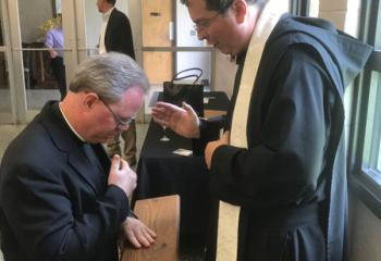Benedictine Father Linus Klucsarits (formerly Paul Klucsarits) offers his first priestly blessing to Msgr. Andrew Baker at the reception after Father Linus' ordination to the priesthood June 3 at St. Bernard's Abbey Church, Cullman, Alabama. (Photo courtesy of Msgr. Andrew Baker)