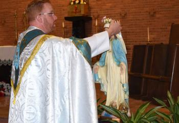 Father Mark Searles crowns the Blessed Mother after the procession. (Photo by John Simitz)