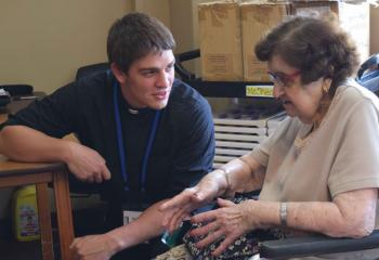 Seminarian Keaton Eidle chats with Holy Family Manor resident Mary Vidonya during the July 18 afternoon visit. (Photo by John Simitz)