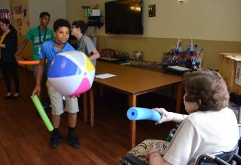 Holy Family Manor resident Mary Vidonya and a Quo Vadis camper play Noodle Ball. (Photo by John Simitz)