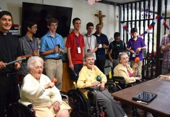 Holy Family Manor residents, from left front, Clare Farrel, Rose Donchez and Elizabeth Mrowinski enjoy playing in the Rhythm Band July 18 with seminarian Giuseppe Esposito, back left, and Quo Vadis participants. (Photo by John Simitz)