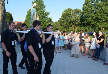 Seminarians carrying the statue of the Blessed Mother during the Rosary Procession July 16 are, from left , Aaron Scheidel, Giuseppe Esposito, Keaton Eidle and Zachary Wehr. (Photo by John Simitz)