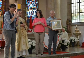 George and Margaret Chovanes, right, parishioners of MBS, present a print of St. Paul's Chapel to Father Michael Paul, pastor of SS. Peter and Paul, and Petra Stahler, interpreter and parishioner of SS. Peter and Paul.