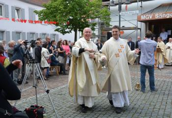 Msgr. Edward Coyle, left, former pastor of MBS, blesses the plaza with Deacon Johannes Hellenbrand.