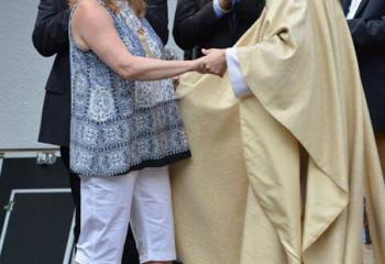 Beth Bakes, left, parishioner of MBS, is greeted by Father Michael Paul at the celebration in the new plaza.