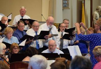 "Beverly McDevitt, right, director of the Cathedral and Diocesan choirs, leads the cathedral's adult choirs – Angelorum Choir, Cathedral Choir, Diocesan Choir and Living Word Choir – in singing the ""Magnificat."" The piece is taken from the Gospel of Luke and is the Blessed Mother's hymn of praise to the Lord."