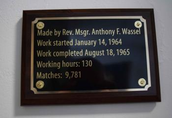 A plaque outside the chapel at HFM display the man hours, time frame and number of matches that went into the creation of the cross. (Photo by John Simitz)