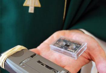 Father Bernard J. Ezaki, parochial vicar at St. Jane Frances de Chantal Church in Easton, Pa., holds the micro-cassette recorder that he uses for Mass prayers, the homily and readings when he celebrates Mass. (CNS photo/Ed Koskey Jr.)