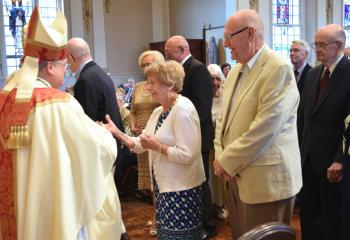Bishop Schlert congratulates Robert and Mary Ann Sterner at the celebration recognizing their 60th wedding anniversary.