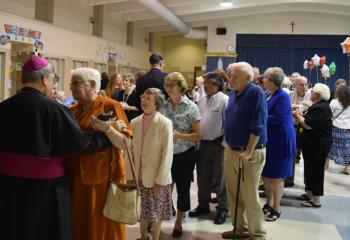 Bishop Alfred Schlert greets faithful from the Berks Deanery during the reception after the Mass.