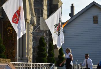 "The Diocesan flag and a flag bearing Bishop Alfred Schlert's coat of arms hang at the entrance of St. Joseph, Jim Thorpe. ""The early fathers of the Church commented that where the Bishop is, there is the Church,"" said Father Francis Baransky."