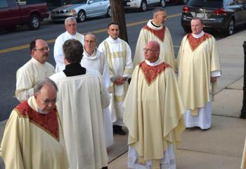 Priests and deacons gather before the Mass.