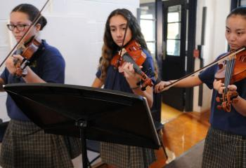 Music Ministry violinists are, from left, Annlisse Lynch, Sahah Atileh and Cathy Young. (Photo by Ed Koskey)