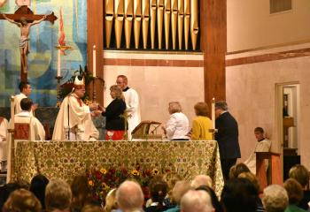Bishop Alfred Schlert receives the gifts.