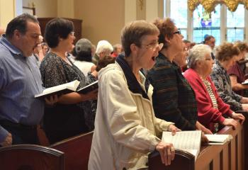 Faithful sing a Marian hymn during the Mass.