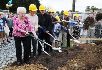 Turning over dirt to clear the way for construction of the new parish center are, from left, Joan Frisch, Jodi Mariano, Father Joseph Tobias, Morgan Halldorson, Blaise Hunt, Stephen Keppel, Ed Perusse and Christine Bruce.