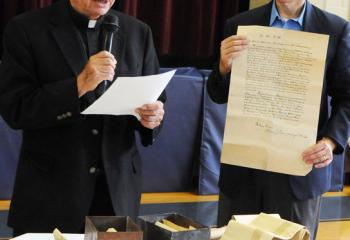 Father Joseph Tobias, left, and Terry Dunne reveal the contents of a time capsule that was secured in the cornerstone of the original church structure. Some of the contents were photos of the local congressman and pastor, letters, and architectural drawings of the church.