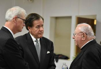 Bishop William Murphy, right, greets Attorney Joseph Zator, left, and Judge Joseph Leeson.