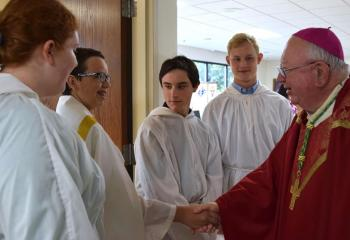 Bishop Murphy greets altar servers, from left, Danielle Dougherty, Kevin Zambito, Daniel Gombar and Reese Griffin.