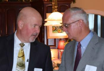 Paul Wirth, board chair of Catholic Charities, left, talks with Michael McGrail during the event.