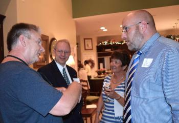 Barry Schmura, left, talks to Gary (Rob) Laubenheimer, case worker for Catholic Charities' Veterans Support Services program. In back are Bob Wert and Joann Schmura.