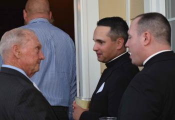 Michael Ehlerman, left, talks with Father Keith Mathur and Father Christopher Butera.