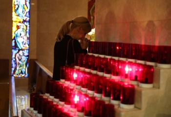 A woman prays during an interfaith memorial service Oct. 2 in Las Vegas for victims of a shooting spree directed at an outdoor country music festival late Oct. 1. A gunman perched in a room on the 32nd floor of a casino hotel unleashed a shower of bullets on the festival below, killing at least 59 people and wounding another 527. (CNS photo/Lucy Nicholson, Reuters)