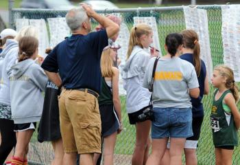 Participants and coaches check race results posted on a fence at the meet.