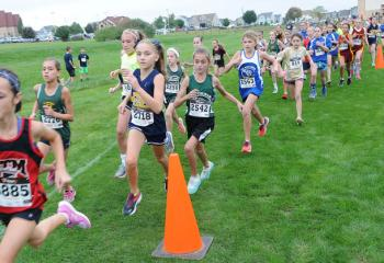 Third- and fourth-grade girls run close together during the meet.