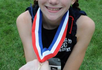 Veronica Gaulai of St. Michael the Archangel School, Bethlehem-Limeport shows the medal she earned for placing first in the fifth- and sixth-grade girls' race.