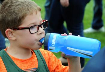 Lincoln Feist of St. Jane drinks from his water bottle after running with kindergarten boys.