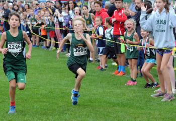 Henry Parrish of St. Ann, Emmaus, left, and Aiden Van Wert of St Jane give it their all as they near the finish of the third and fourth grades boys' race.