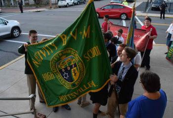 Students from Nativity BVM High School, Pottsville lift their school flag before processing into St. Clare Church.