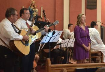 Jessica Jansson sings a hymn with a string quartet during Holy Communion. A 50-member deanery choir joined together to practice for several weeks before performing selections at the Mass.